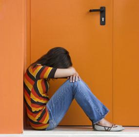 Девушка одиноко сидит под дверьми
