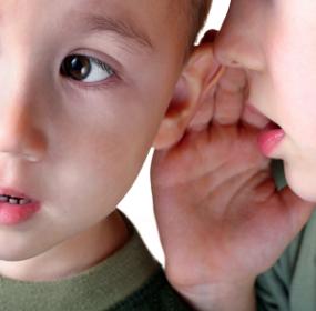 Маленький мальчик шепчет на ухо младшему брату