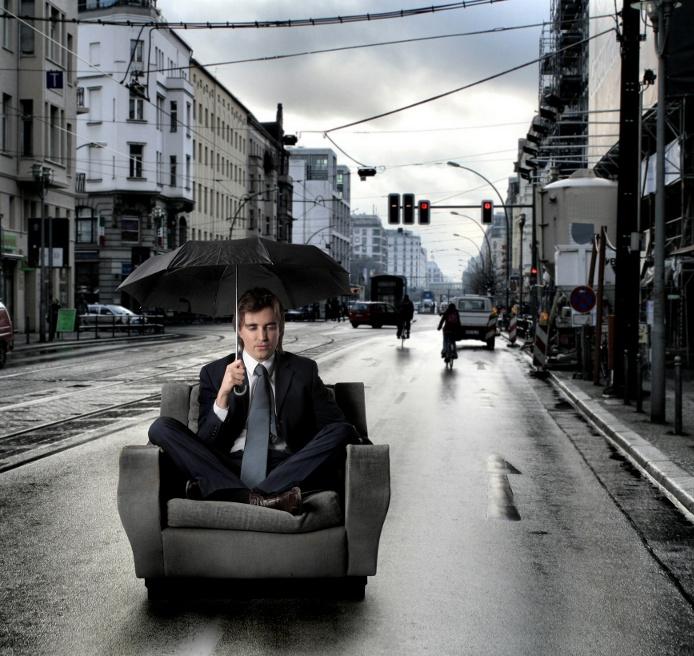 Мужчина в кресле под зонтиком на улице